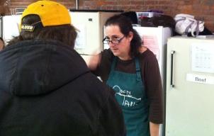 Volunteer helps guest select food item.